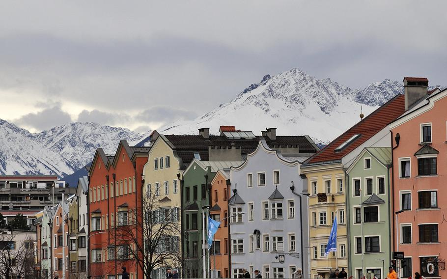 A view of the beautiful and colorful Innsbruck city buildings along the River Inn, with the magestic Alps complementing  the view.
