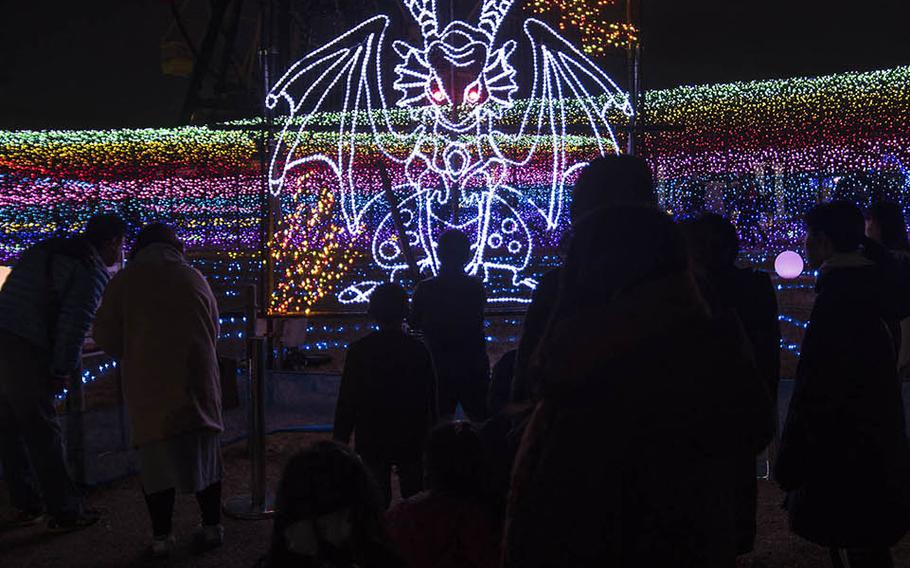 A child slays an illuminated dragon at one of the many interactive light displays at the Tokyo German Village theme park in Chiba prefecture.