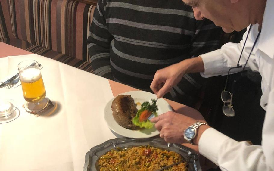 Waiter Luigi Scandali serves a customer a dish called a Merry Bosnian at the Balkan Grill restaurant in Kaiserslautern. The rolled steak is served with djuvec, a flavorful rice-and-vegetable stew.