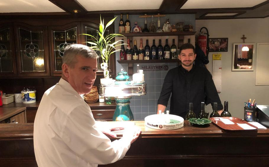 Waiter Luigi Scandali and barman Nikola Petrovic prepare slivovitz, a strong plum-based brandy, at the Balkan Grill lrestaurant  in Kaiserslautern.