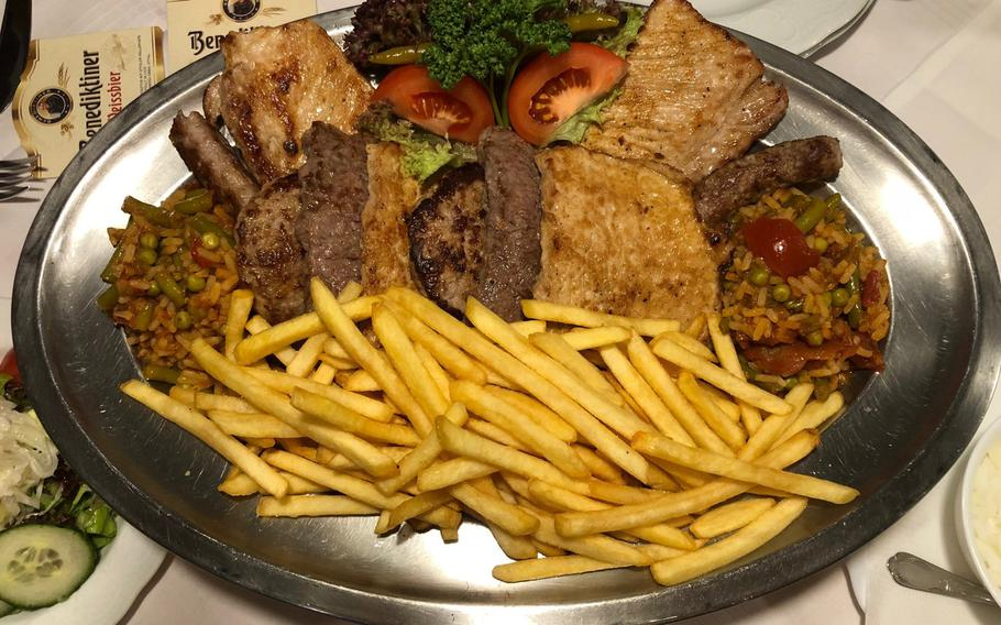 A Balkan Platter for two -- a tray with various grilled meat and salad -- garnished with djuvec, a flavorful rice-and-vegetable stew.