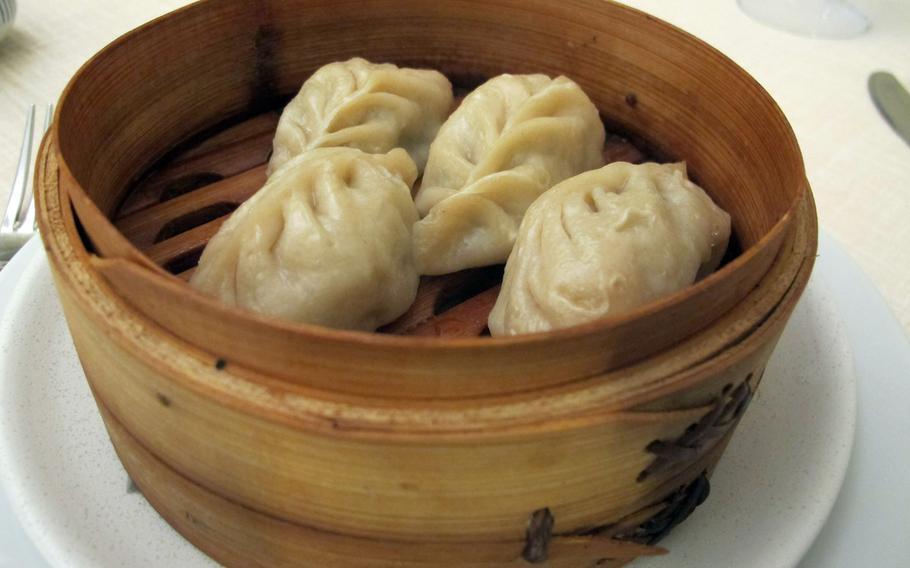 Steamed dumplings at Cicchetteria Cinese Zhu, Vicenza's new Chinese restaurant, arrives hot and pillowy in a wood bowl.