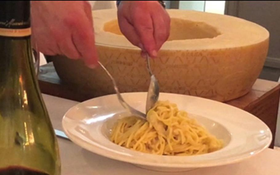 Pasta is scooped into a shallow bowl after being mixed in a hollowed out wheel of Parmesan cheese at the Italiano Sapori Veri restaurant in Kaiserslautern, Germany.
