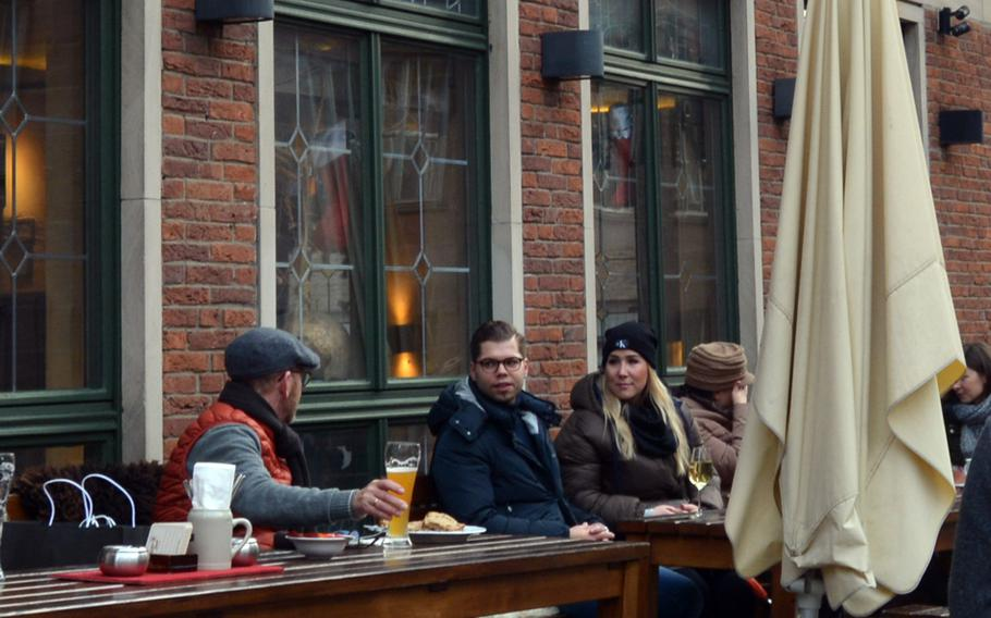 A few people relax with beer and bratwurst outside Roeslein in Nuremberg, Germany, on Dec. 21, 2019.