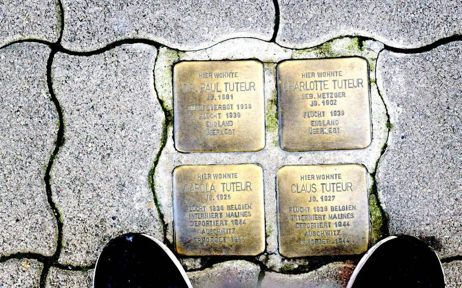 """Four Stolpersteine on Alleestrasse in Kaiserslautern remember the Tuteur family. The word """"ueberlebt"""" - German for survived - is inscribed at the bottom of the parents' stones, while the inscription on the stones of Carola and Claus, their children, says, """"Murdered at Auschwitz."""""""
