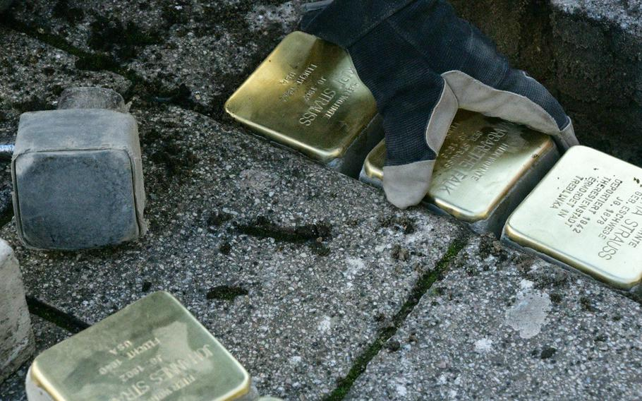 Artist Gunther Demnig places a Stolperstein in a hole in the sidewalk on Eisenbahnstrasse in Kaiserslautern, Germany, on Wednesday, February 5, 2020. The 4 x 4-inch brass squares, which are in 1,200 German cities and towns and 23 European countries, remember victims of Nazi persecution like the Strausses, who were Jewish.