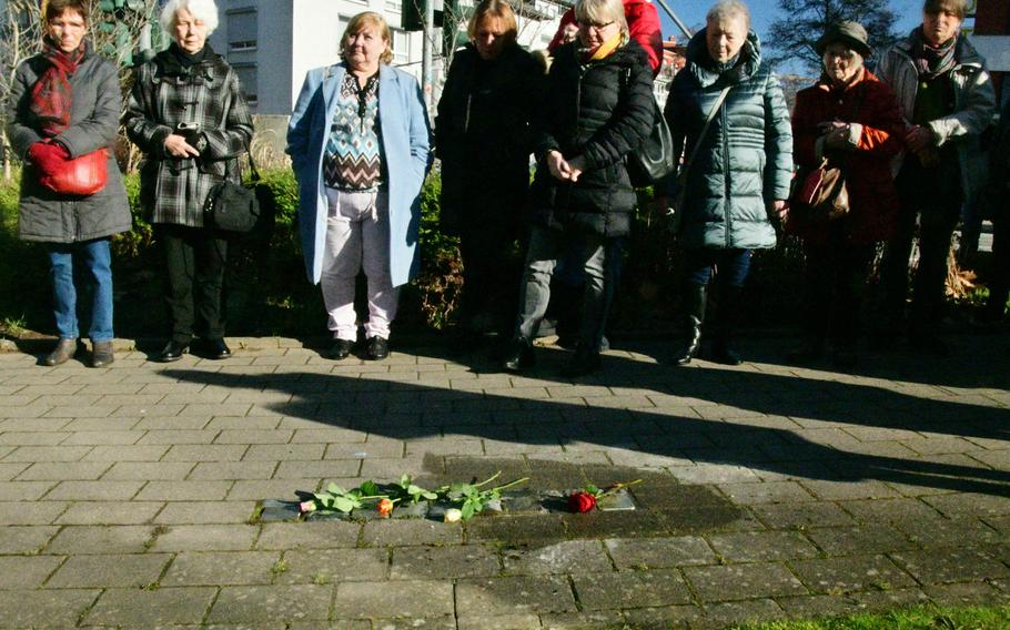 A group of people listen to speeches after a new Stolperstein - small memorials to victims of Germany's World War II Nazi regime - is added to several laid previously at Philipp-Mees-Platz near the police headquarters in Kaiserslautern, Germany, on Wednesday, February 5, 2020. The Stolpersteine laid here honor the memories of political opponents of the Nazis.