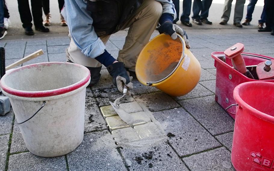 Artist Gunther Demnig applies concrete to Stolpersteine he just laid in the sidewalk on Eisenbahnstrasse in Kaiserslautern on Wednesday, February 5, 2020. The five stones outside a business in downtown Kaiserslautern memorialize Theodor and Bertha Strauss, who were killed at Treblinka death camp, built and operated by Nazi Germany in occupied Poland, and their children, who escaped to the U.S.