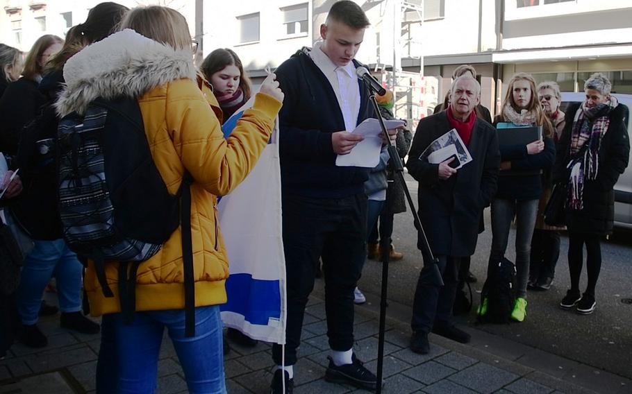 """German high school students from the Westpfalzrealschule Weilerbach read out biographies of the Strauss family during the laying of a Stolperstein in their memory on Wednesday, February 5, 2020, in Kaiserslautern, Germany. Kaiserslautern has 152 brass Stolpersteine - literally """"stumble stones"""" - which tell brief stories of people like the Strausses, who were were among millions of Jews who were victimized by Germany's Nazi regime."""