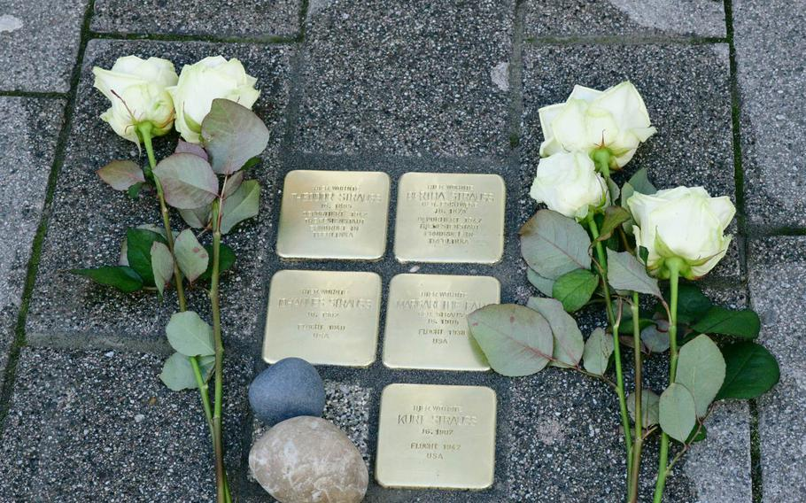 White roses lie by the Stolpersteine laid Wednesday, February 5, 2020 on Eisenbahnstrasse in Kaiserslautern, Germany, memorializing the Strauss family. The parents were deported to Theresienstadt in what is now the Czech Republic and then to Treblinka in Poland, where they were murdered, but the three children fled to the U.S. and survived the Holocaust.
