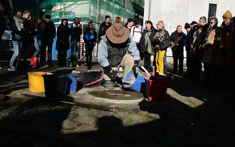 Artist Gunther Demnig applies concrete to Stolpersteine he's just laid in the sidewalk on Baumstrasse in Kaiserslautern on Wednesday, February 5, 2020. The stones memorialize the Goetz family, who fled Nazi Germany to the United States in 1935.
