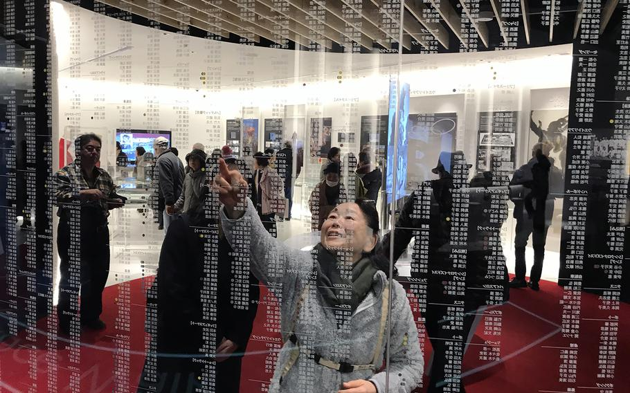 A woman points to the name of a past Japanese Olympian at the Japan Olympic Museum in Tokyo, Jan. 22, 2020.