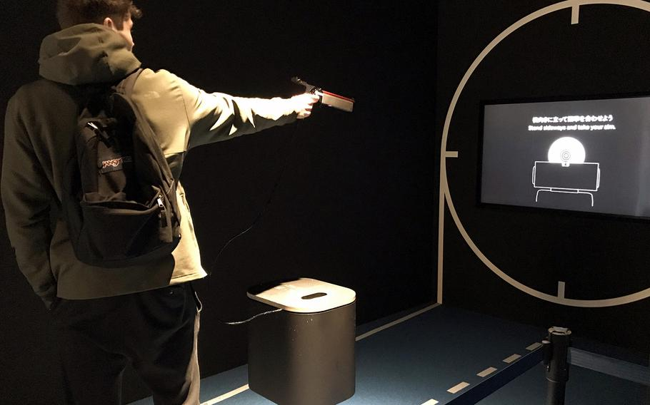 A visitor to the Japan Olympic Museum in Tokyo tries out a shooting simulator that allows people to compare their aim to an Olympic athlete, Jan. 22, 2020.