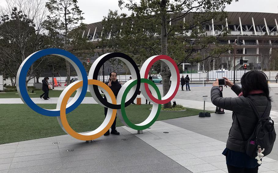 A visitor to the Japan Olympic Museum poses with the Olympic rings near the new National Stadium in Tokyo, Jan. 22, 2020. The stadium will host many events, including the opening and closing ceremonies, for the Summer Games.