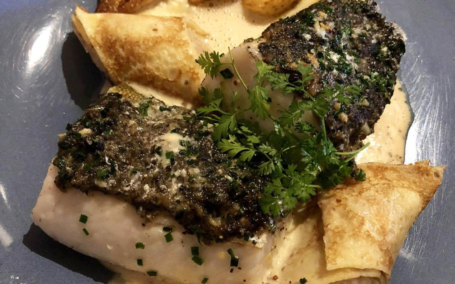 A pike-perch fillet with Lorraine snails, sauerkraut pancake and white butter with mustard, as served at the Strasbourg restaurant in Bitche, France.