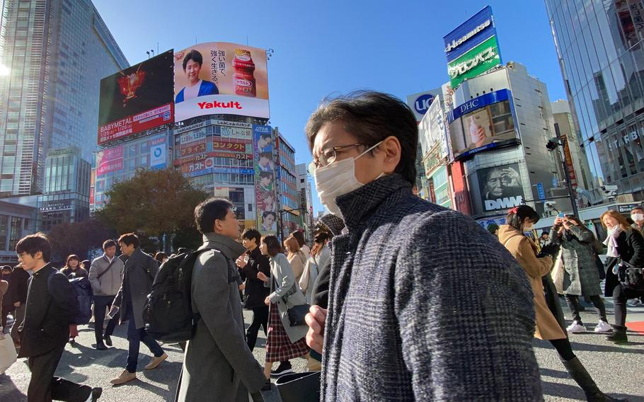 Tokyoites and tourists walk across the popular Shibuya Scramble intersection in central Tokyo in November 2019.