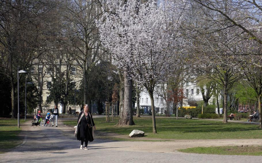 People walk through one of the parks that make up the Wallanlagen in Frankfurt am Main, Germany. The Wallanlagen is a greenbelt of parks surrounding the center of Frankfurt, north of the Main River, where the city's defensive walls once stood.