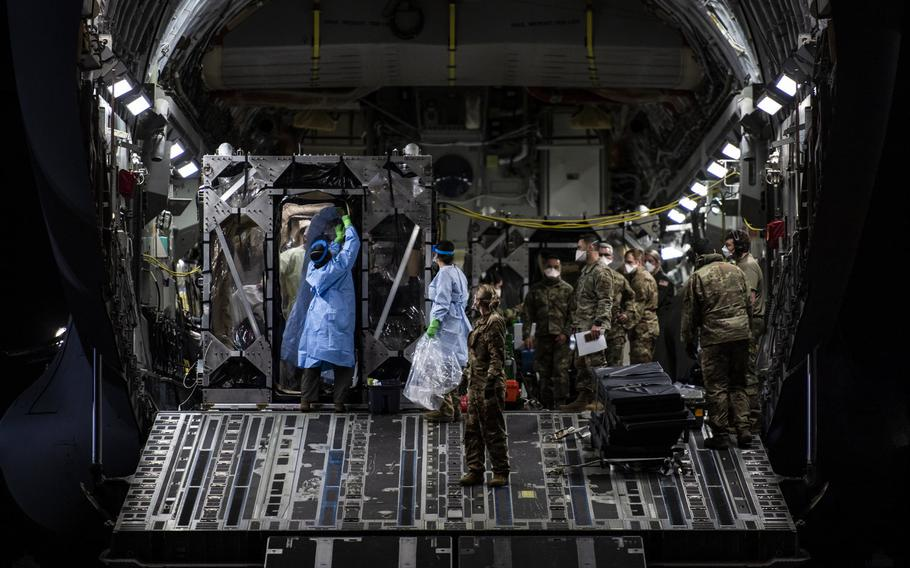 Airmen prepare to offload coronavirus patients at Ramstein Air Base, Germany, April 10, 2020, during the first-ever operational use of the Transport Isolation System. The TIS is an infectious disease containment unit designed to minimize contamination risk to aircrew and medical attendants, while allowing in-flight medical care for patients with an infectious disease.