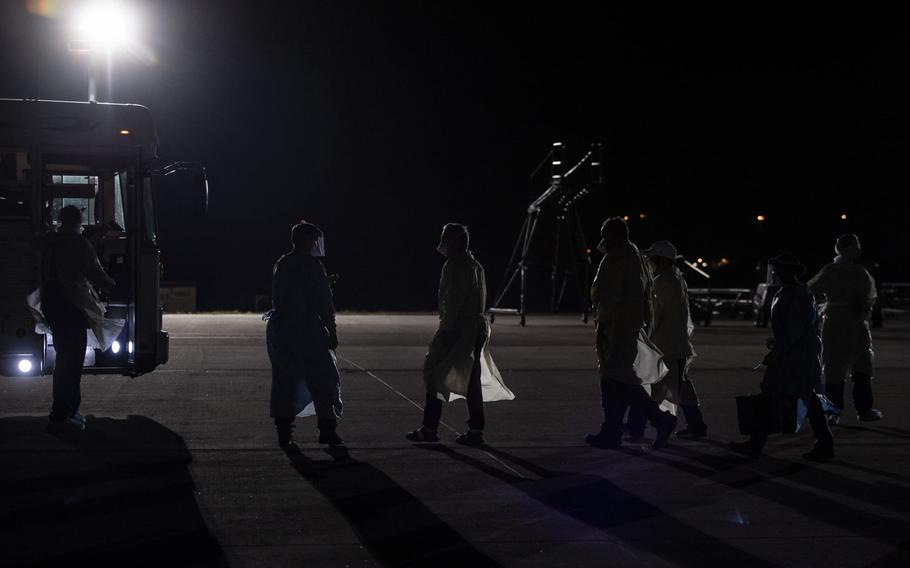 U.S. Air Force airmen escort coronavirus patients to a medical bus at Ramstein Air Base, Germany, April 10, 2020. An infectious disease containment unit developed to safely transport Ebola patients during the 2014 West Africa outbreak was used for the first time to transport three U.S. government contractors who have tested positive for the coronavirus, from Afghanistan.