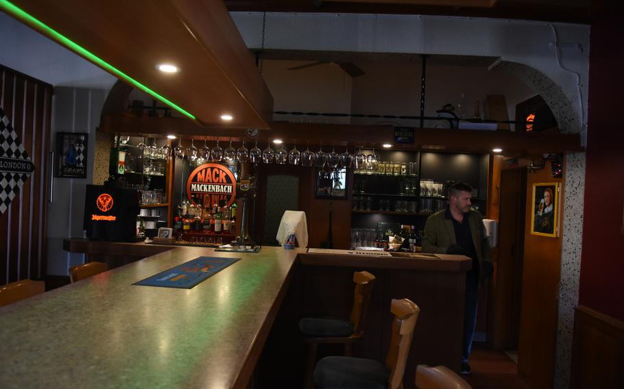Neil Burton, the owner of Neil's Pub in Mackenbach, Germany, stands behind an empty bar inside his restaurant. The pub is only doing takeout during the evening hours from Tuesday to Saturday while coronavirus restrictions remain in effect.