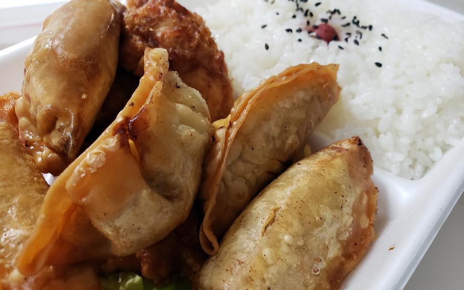 The $5 gyoza bento from Lunch House Turtle, a takeout eatery near Yokota Air Base in western Tokyo, includes five deep-fried pot stickers, sliced fried chicken breast and a large portion of rice.