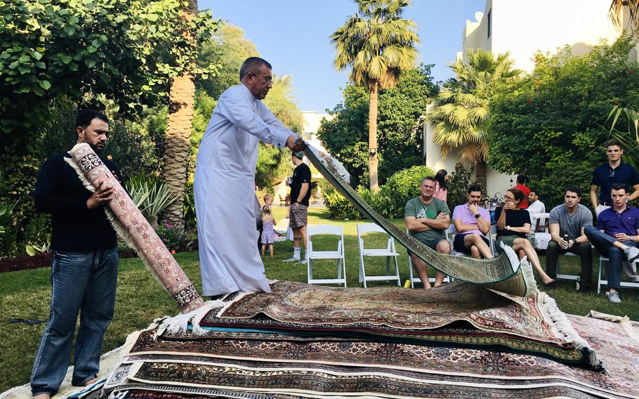 Mohammed Abdu Al-Omari rolls out a carpet during a ''rug flop'' event in Bahrain, hosted by U.S. Navy Cmdr. Joe Zerby and his wife, Jill.