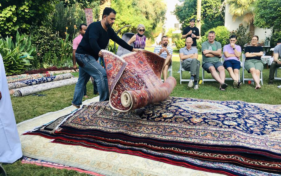 Mustafa Ameen, from the Carpet House in Adliya, Bahrain, rolls out a carpet during a ''rug flop'' event hosted by U.S. Navy Cmdr. Joe Zerby and his wife, Jill.