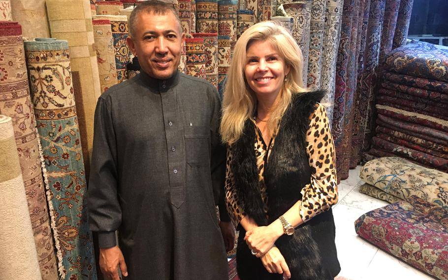 Carpet House owner Mohammed Abdu Al-Omari and U.S. Navy spouse Jill Zerby pose for a photo in front of rolled carpets.