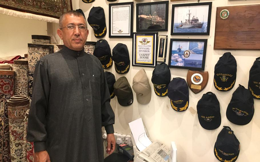 Carpet House owner Mohammed Abdu Al-Omari poses for a photo in front of a some U.S. Navy command ball caps.