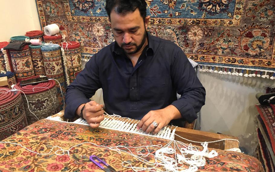 Mustafa Ameen repairs a carpet at the Carpet House in Adliya, Bahrain.