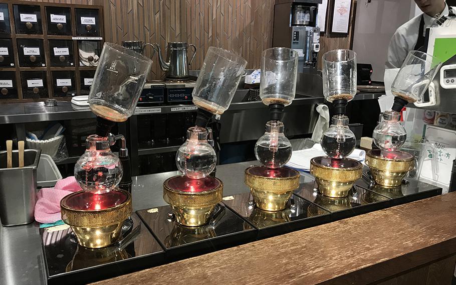 Syphon-style coffee brewers await customers' orders at Kurashiki Coffee in Sasebo, Japan.