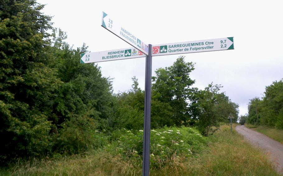 Signs in a village on the border between Germany and France point in different directions, indicating bike paths and where they lead. In some villages, the signs are much smaller and less informative.