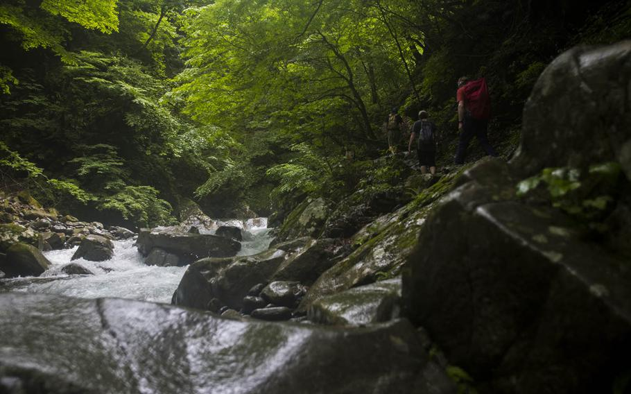 Hikers traverse the sometimes slippery trail of the Nishizawa Gorge in Yamanashi prefecture, Japan, July 7, 2020.