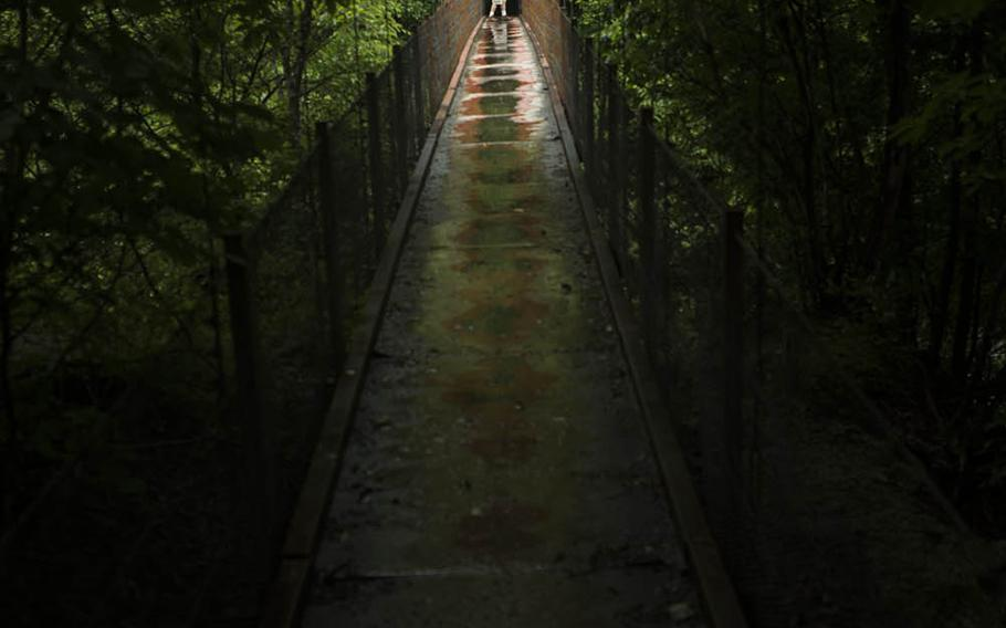 A hiker takes photos from a suspension bridge over the Fuefuki River while trekking to Nishizawa Gorge in Yamanashi prefecture, Japan, July 7, 2020.