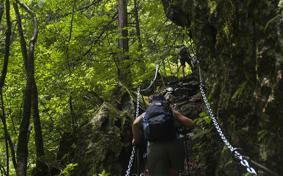 Yokota High School teacher Jenny Gaume uses a chain railing during her hike to Nishizawa Gorge in Yamanashi prefecture, Japan, July 7, 2020.