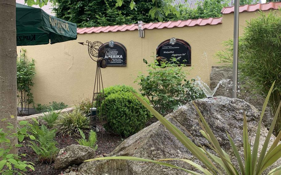 At the restaurant Zum Stich'n, there is a fountain with plants that makes for a pleasant dining experience in Grafenwoehr, Germany.