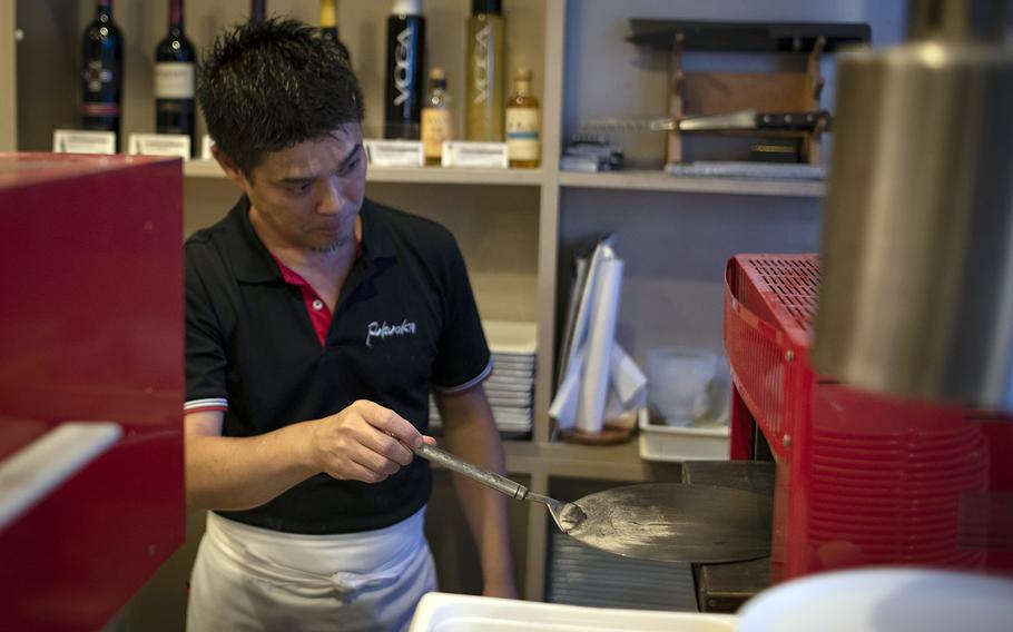 Yoshinobu Fukuoka, who has been in the restaurant business for nearly 30 years, prepares a meal at his namesake eatery, Fukuoka Pizza, in Iwkauni, Japan, June 26, 2020.