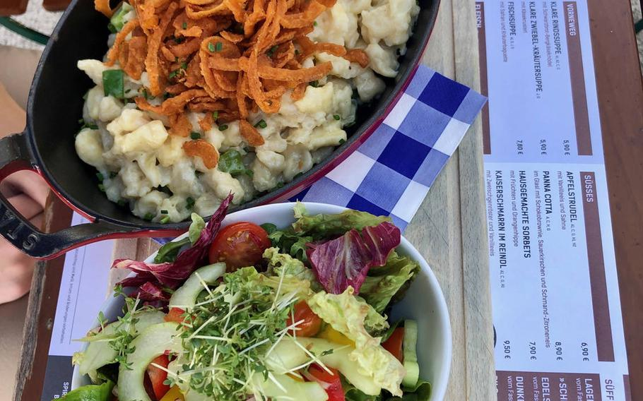 A dish of Kasspatzen, the Bavarian version of gnocchi, served with roasted onions and salad.