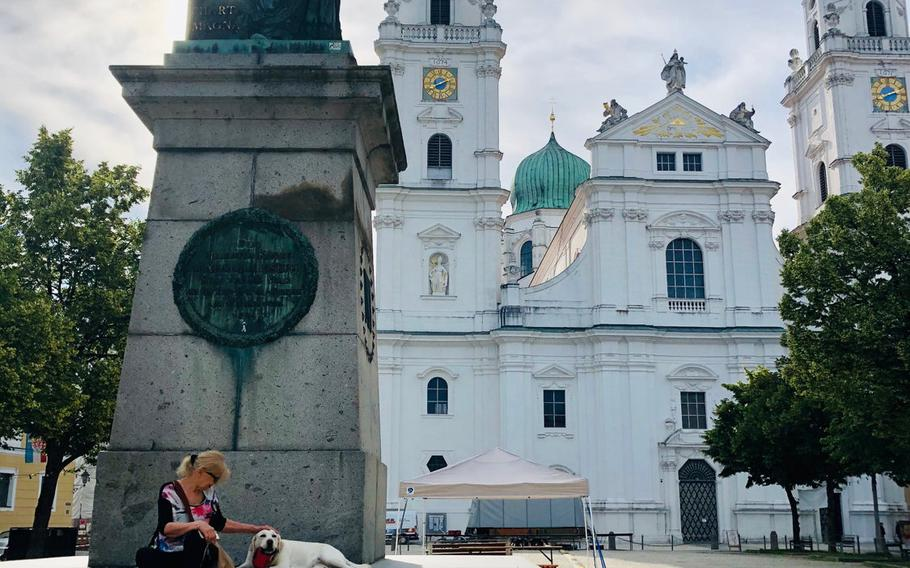 A visitor and her dog take a break at the foot of the monument to Bavarian King Maximilian I Joseph in the square outside the cathedral in the center of Passau's medieval old town.