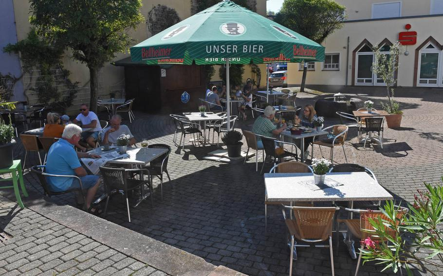 Outdoor seating at ZeitLos Cafe and Bistro in Rodenbach, Germany, is in a cozy courtyard away from the village's main street. Umbrellas over the tables provide ample shade from the sun.