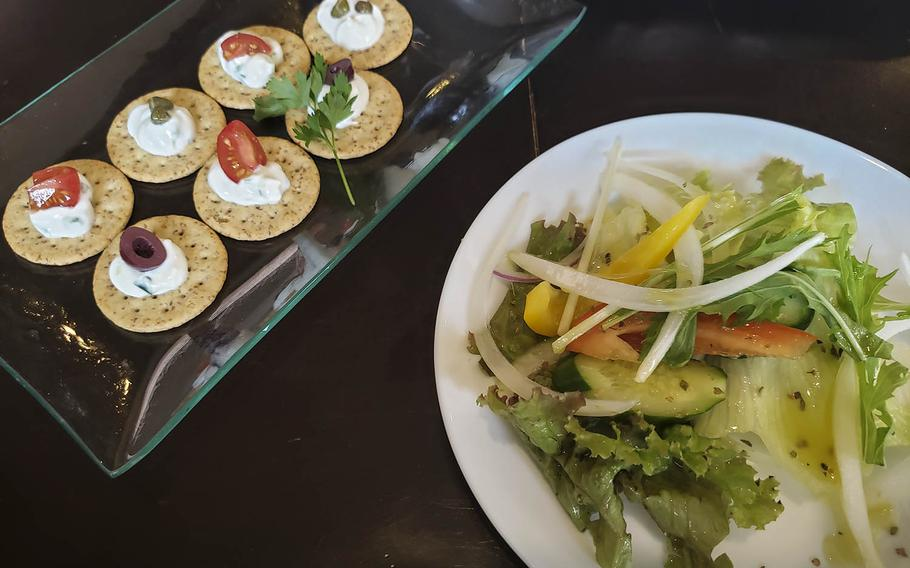 The tzatziki, left, from Shupoul in Tachikawa, Japan, consists of six crackers with a dollop of the Greek yogurt and cucumber sauce, each with a caper, kalamata olive slice or chunk of cherry tomato.