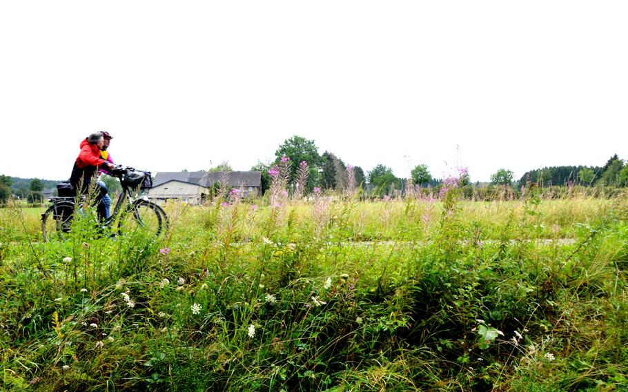 A couple rides past a farm and wildflowers on the Vennbahn bike path near Monschau, Germany, on Sept. 1, 2020, about 100 yards from one of many points where it crosses into Belgium. The path goes from Aachen, Germany, in the north to Troisvierges, Luxembourg in the south, via Belgium.