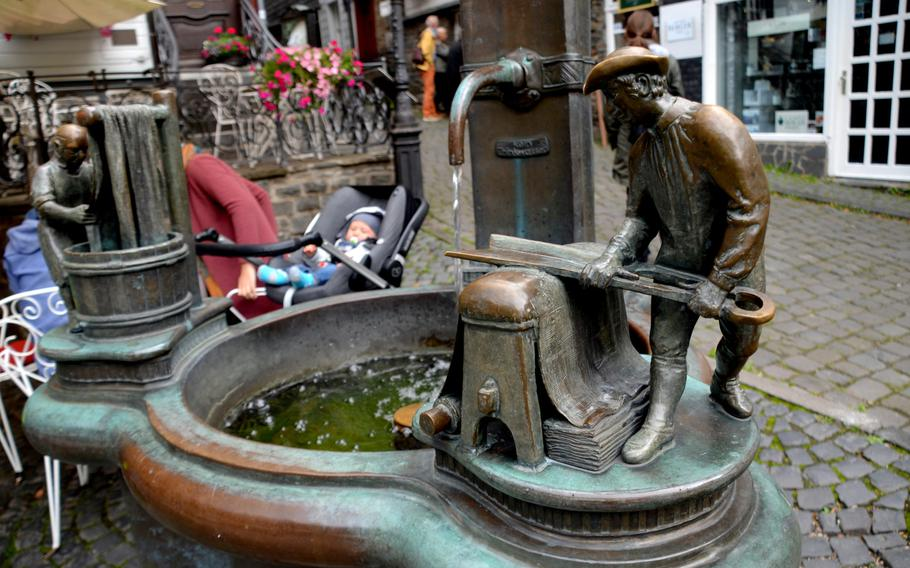 A fountain in the center of Monschau, Germany, depicts the town's past as a hub for textile production. Monschau lies near Germany's western border with Belgium, below the 100-mile Vennbahn bike path, which runs from Aachen in Germany, through Belgium, to Troisvierges in Luxembourg.