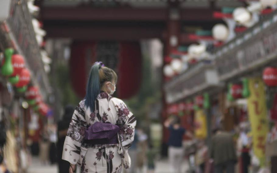A woman wears a casual summer kimono called a yukata as she walks toward Sensoji, a popular Buddhist temple in the Asakusa section of central Tokyo, Sept. 1, 2020.