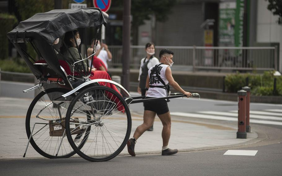 A rickshaw driver gives a tour of Asakusa, an old district of Tokyo known for the Sensoji Buddhist temple, Sept. 1, 2020.