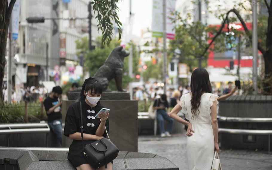 People hang out near the Hachiko statue outside Shibuya Station in Tokyo, Sept. 2, 2020. Hachiko was an Akita dog remembered for remarkable loyalty to his owner, whom he waited for outside the station for nearly a decade after his death.