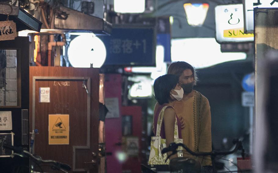 People leave an establishment in the Golden Gai bar district of Shinjuku, Tokyo, Sept. 2, 2020. Golden Gai comprises several narrow alleyways that are home to more than 200 tiny bars, many of which can serve only a few customers at a time.