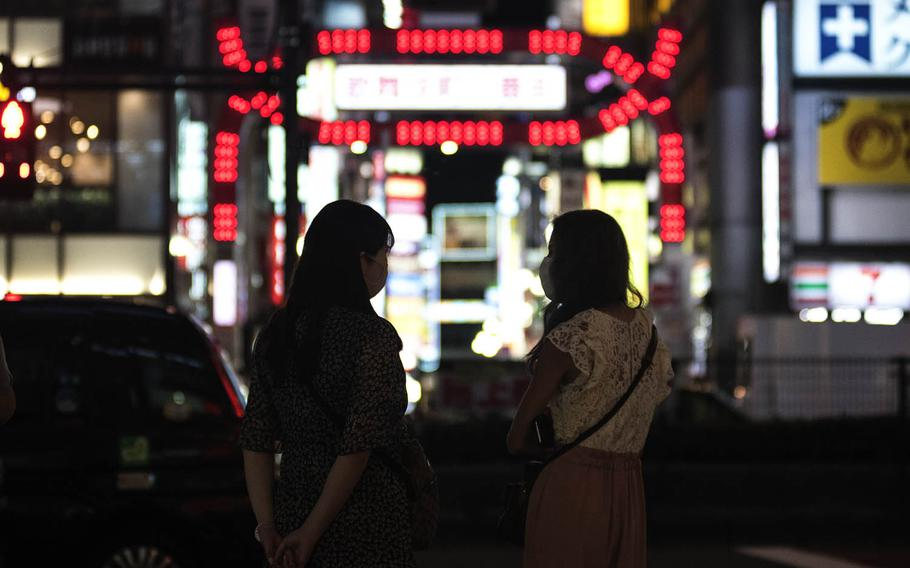 Friends chat outside the gateway to the Kabukicho entertainment and red-light district in the Shinjuku section of Tokyo, Sept. 2, 2020. The district is known for its movie theaters, game centers, restaurants, nightclubs and some seedier establishments.