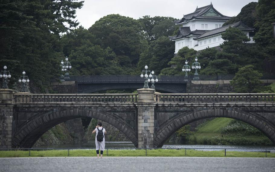 A lone visitor stands outside the iconic bridges leading into the inner Imperial Palace grounds in central Tokyo, Sept. 3, 2020. Most of the site is closed to the public, except for New Year's Day and the Emperor's Birthday. It's also possible to take reserved guided tours.