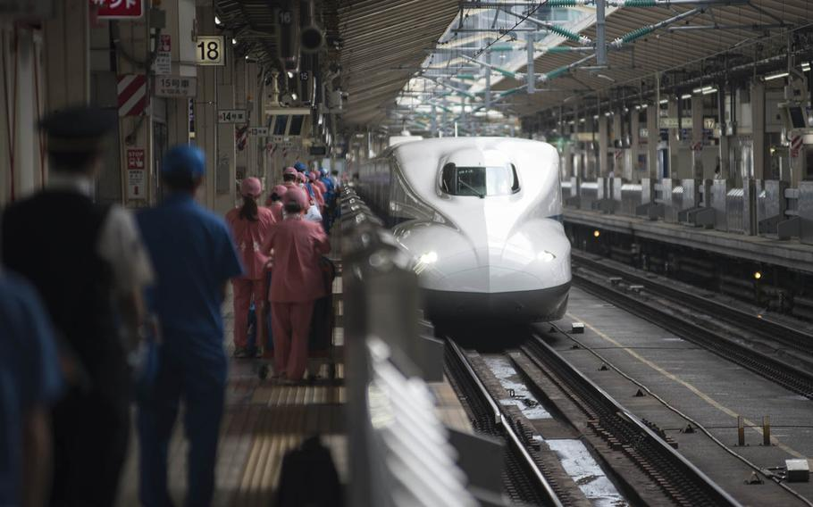 Shinkansen conductor and cleaning staff, wearing the pink uniforms, wait to board an incoming bullet train at Tokyo Station, Sept. 3, 2020. The trains can reach speeds of nearly 200 mph and are lauded as a fast, convenient way to travel throughout Japan.